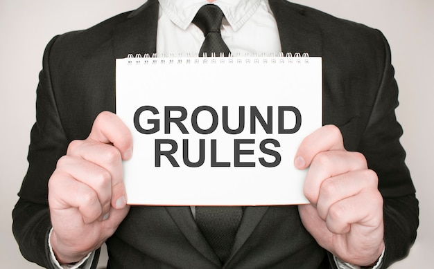 Businessman holding a notepad with text ground rules