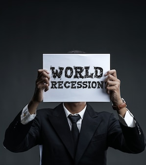 Businessman holding paper covering his face with  world recession text
