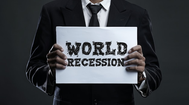 Businessman holding paper with  world recession text