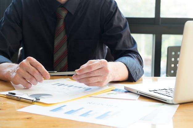 Бизнесмен, проведение перо, анализ графики инвестиций с ноутбуком.