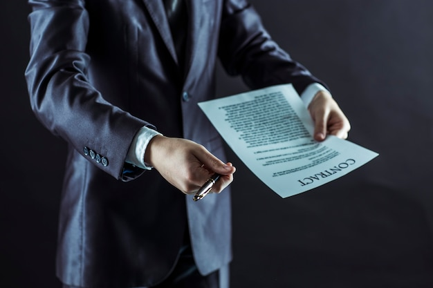 Businessman holding a pen and a document with the terms of the contract.