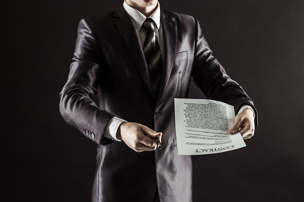 Businessman holding a pen and a document with the terms of the contract
