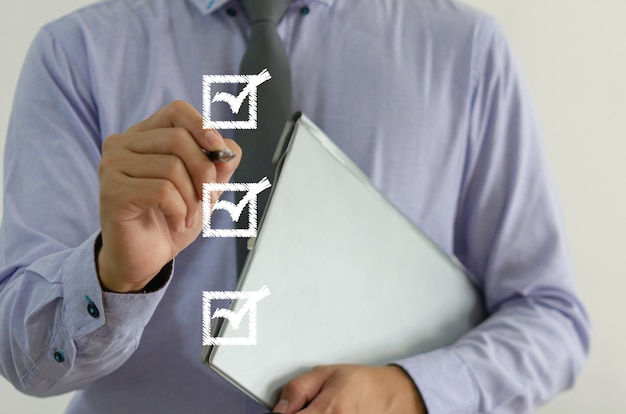 Businessman holding a pen with a check mark on the square on a virtual screen