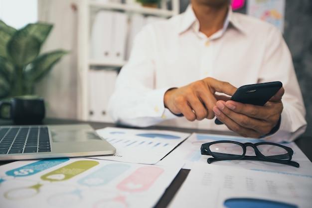 Бизнесмен, держащий телефон на рабочем столе