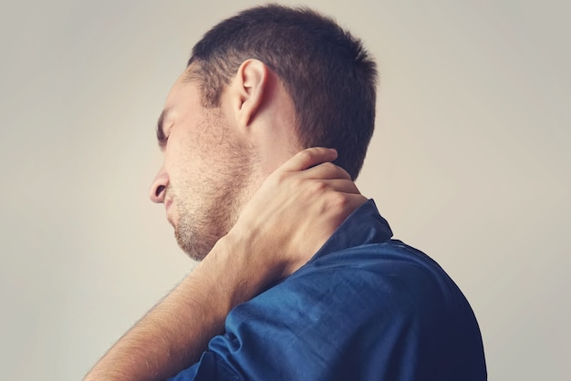 Businessman holding a phone and her neck with pain. young guy holding his neck. a sore neck. chondrosis. the concept of health. fracture of the cervical spine