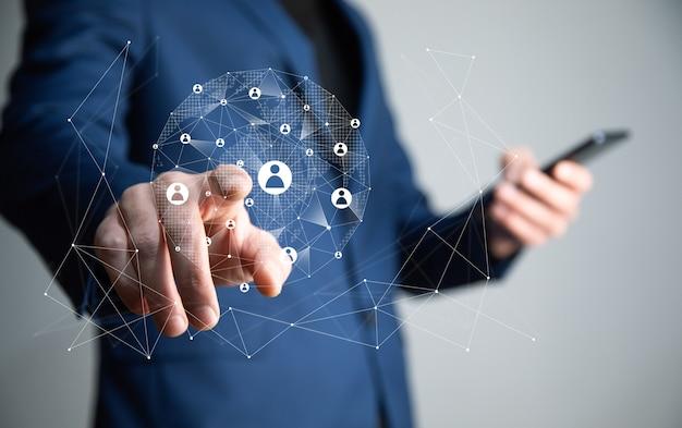 Бизнесмен, держащий телефон со структурой иконок сети социальных сетей