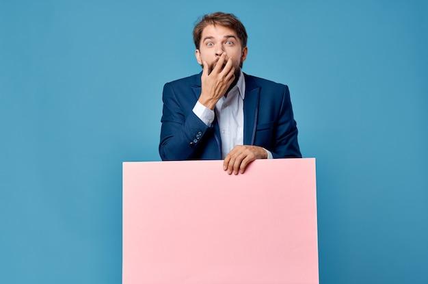 青い背景にピンクの販促看板を保持しているビジネスマン。