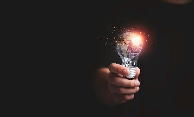 Бизнесмен, держащий планету внутри лампочки на день земли и концепция сохранения энергии окружающей среды, элемент этого изображения из наса и 3d визуализации.