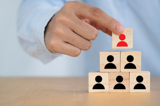 Businessman holding and putting print screen red illustration human wooden block to the top black illustration human wooden blocks. it is leadership.
