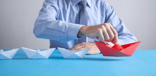 흰색 보트와 빨간 종이 접기 종이 보트를 들고 사업가. 비즈니스, 리더십