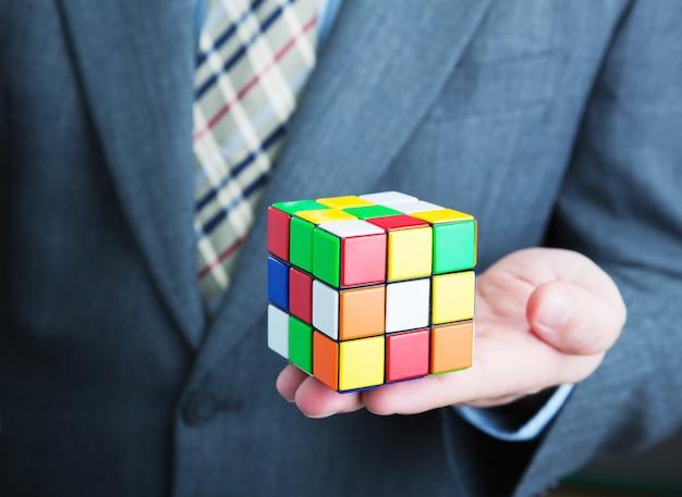 Businessman holding rubik cube closeup picture