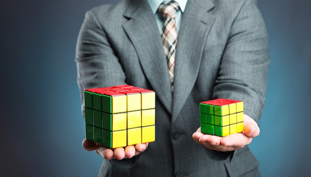 Businessman holding rubik cube in his hands, closeup picture