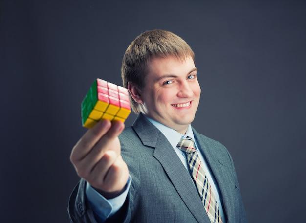 Бизнесмен, держа в руках кубик рубика