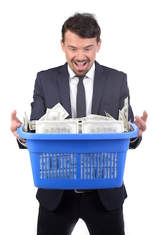 Businessman holding a shopping cart full of money.