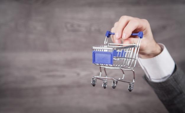 Businessman holding shopping cart. shopping