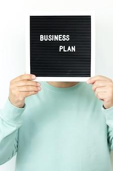 Бизнесмен, держащий вывеску с текстом «бизнес-план». концепция предпринимательства