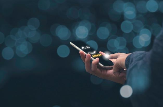 スマートフォンを持って、5つ星の顧客のオンライン評価結果を示すビジネスマン。