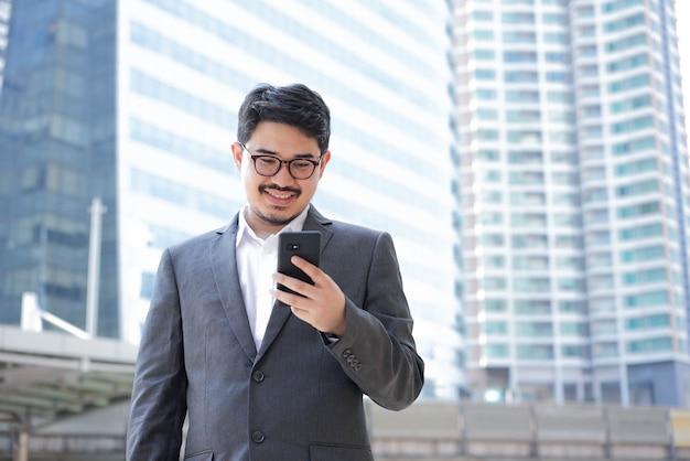 Бизнесмен, держащий смартфон и стоящий за пределами здания