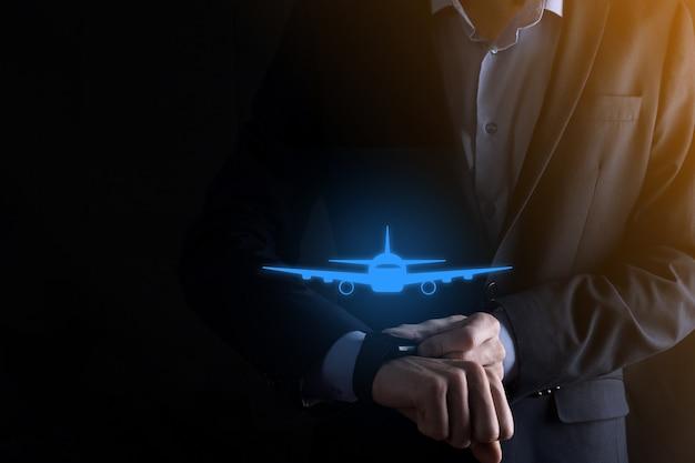 スマートフォンの手に飛行機のアイコンを持っているビジネスマン。オンラインチケット購入。旅行。