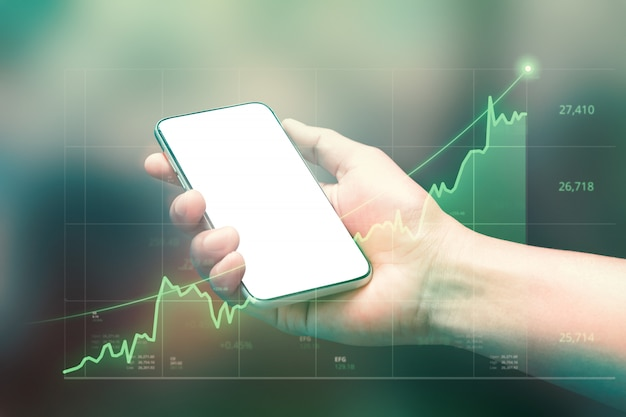 Businessman holding smartphone and showing holographic graphs and stock market statistics gain profits.