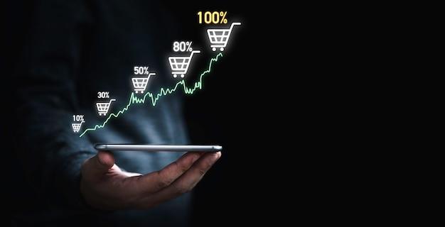 オンライン販売事業の成長コンセプトを高めるための仮想グラフチャートとショッピングトロリーカートを表示するスマートフォンを保持しているビジネスマン。