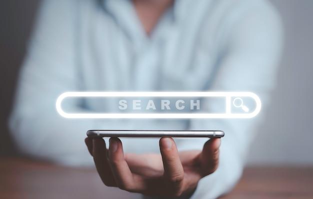 Бизнесмен, держащий смартфон с виртуальным браузером поисковой системы, концепцией информационных технологий.