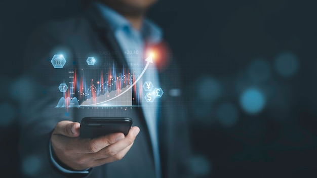 Businessman holding smartphone with  virtual technical graph and chart for analysis stock market, technology investment and value investment concept.