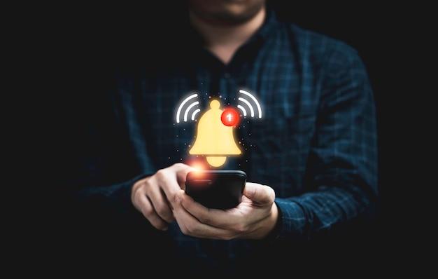アプリケーション通知アラートの概念のための仮想黄色のベルが鳴っているスマートフォンを保持しているビジネスマン。