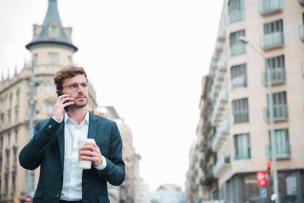 Бизнесмен держа стоять на улице держа кофейную чашку на вынос в руке говоря на мобильном телефоне
