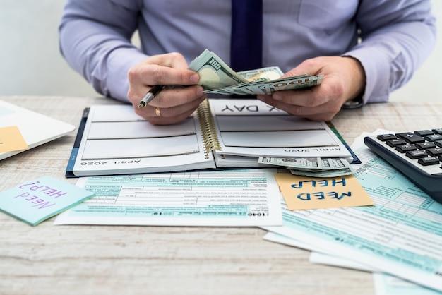 碑文のステッカーを保持しているビジネスマン米国の税務フォーム1040に記入し、お金を数えるのに助けが必要です。納税申告書私たちビジネス収入オフィスハンドフィルの概念