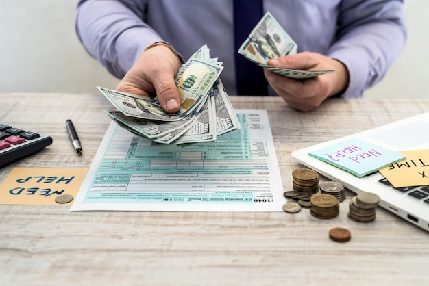 碑文のステッカーを保持しているビジネスマンは、米国の税務フォーム1040に記入し、お金を数えるのに助けが必要です。税務フォーム私たちビジネス収入オフィスハンドフィルの概念