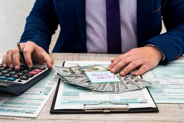 碑文のステッカーを保持しているビジネスマンは、米国の税務フォーム1040に記入し、お金を数えるのに助けが必要です