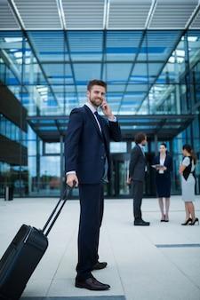 Бизнесмен держит чемодан на мобильном телефоне