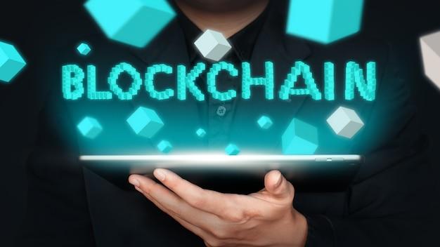 タブレットとブロックチェーンの言葉を持っているビジネスマン、支払いなどの世界のビジネスを変えるテクノロジーブロックチェーン。ブロックチェーンの概念、ビジネスの概念、技術の概念