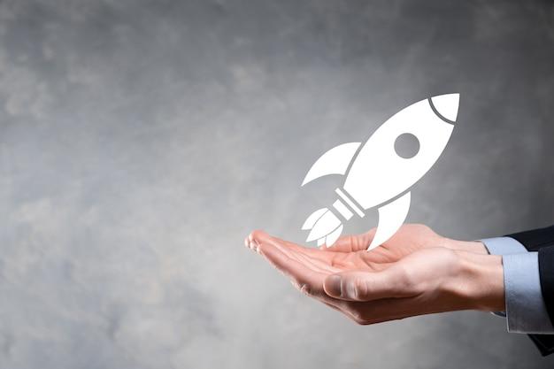 タブレットとアイコンのロケットを持っているビジネスマンが起動し、暗い背景のネットワーク接続で画面から飛び出します。