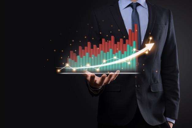 태블릿을 들고 어두운 배경에 위쪽 화살표와 통계, 그래프 및 차트의 성장 가상 홀로그램을 보여주는 사업가. 주식 시장. 비즈니스 성장, 기획 및 전략 개념.