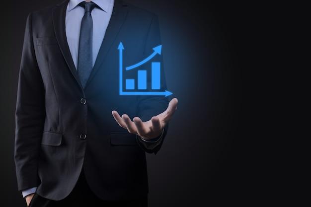 タブレットを持って、暗い背景の上に矢印で統計、グラフ、チャートの成長する仮想ホログラムを表示しているビジネスマン。株式市場。ビジネスの成長、計画および戦略の概念。