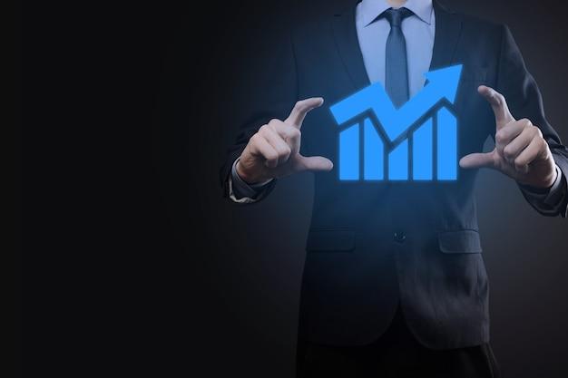 태블릿을 들고 어두운 배경에 화살표가 있는 통계, 그래프 및 차트의 성장하는 가상 홀로그램을 보여주는 사업가입니다. 주식 시장. 비즈니스 성장, 계획 및 전략 개념입니다.
