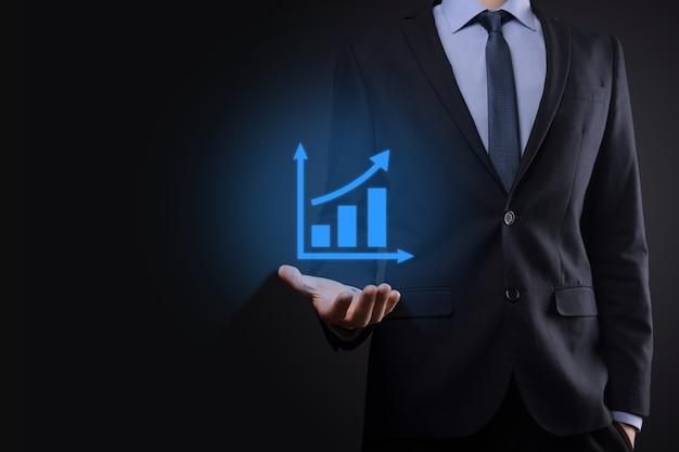 Бизнесмен, держа планшет и показывая растущую виртуальную голограмму статистики, графика и диаграммы со стрелкой вверх на темном фоне.