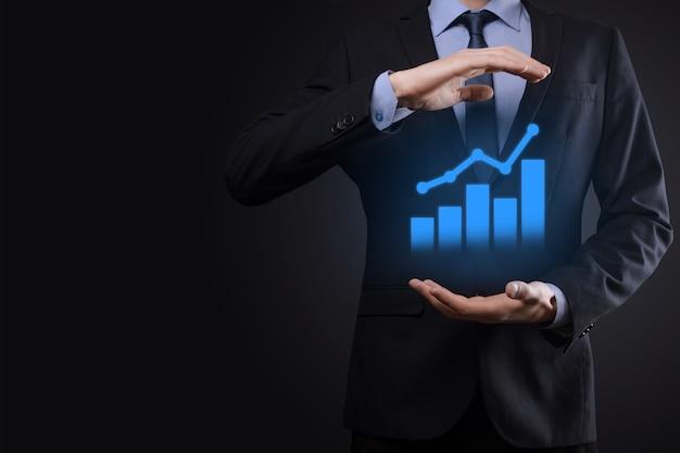 タブレットを持って、暗い壁に上向き矢印で統計、グラフ、チャートの成長する仮想ホログラムを示すビジネスマン。株式市場。ビジネスの成長、計画および戦略の概念。