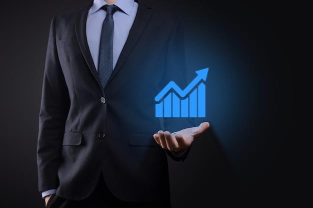 タブレットを持って、暗い壁に上向き矢印で統計、グラフ、チャートの成長する仮想ホログラムを表示しているビジネスマン。株式市場。ビジネスの成長、計画および戦略の概念。