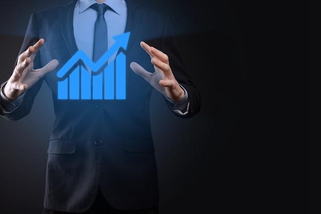Бизнесмен, держащий планшет и показывающий растущую виртуальную голограмму статистики, графика и диаграммы со стрелкой вверх на темной стене. фондовый рынок. бизнес-концепция роста, планирования и стратегии.