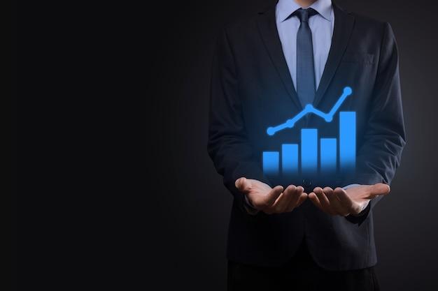 Бизнесмен держит планшет и показывает растущую виртуальную голограмму статистики