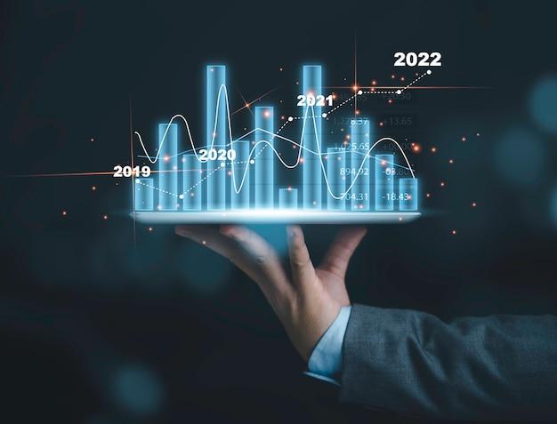 Бизнесмен, держащий таблетку с красивой гистограммой и линейной диаграммой, экономической и деловой концепцией инвестиций в акции.