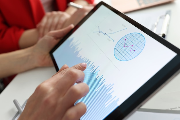 Businessman holding tablet with charts and diagrams in his hands at workplace