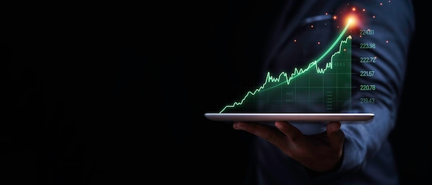 Businessman holding tablet with increasing virtual investment graph and chart for stock market analysis trend and technical by trader concept.