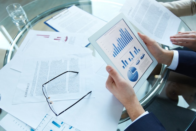 Businessman holding a tablet with statistical data