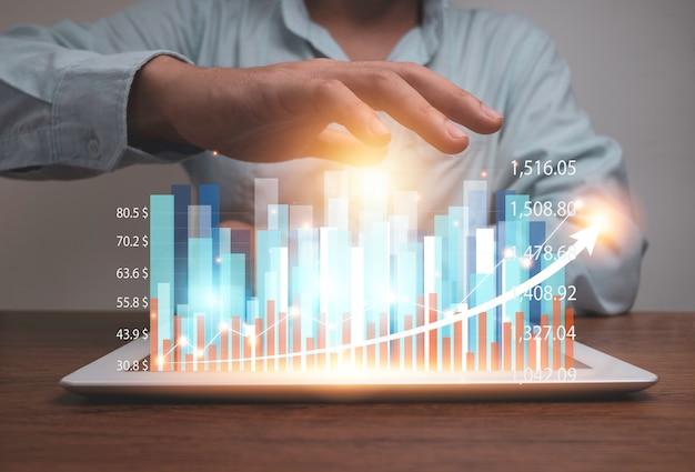 仮想統計ホログラムグラフとチャートのタブレットを保持している実業家。