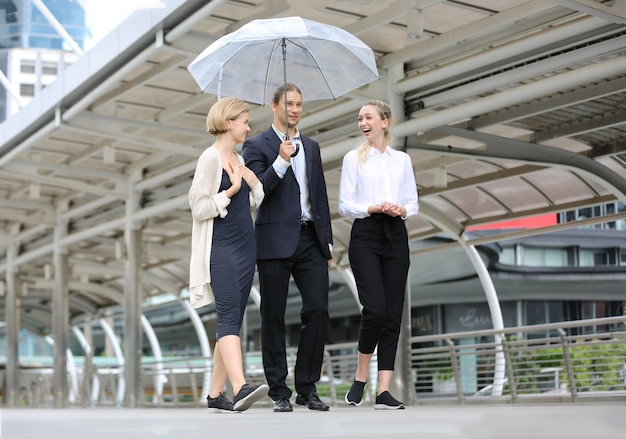 A businessman holding umbellra for two businesswomen and discussing while walking on street for lunch.