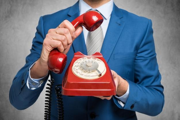 Businessman holding a vintage phone